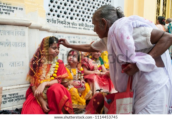 KOLKATA- MARCH  27: An old widowed woman taking blessing from a girl child during Kumari (young unmarried Hindu girl) Puja festival in Adyapith near Kolkata on 27th March, 2015.