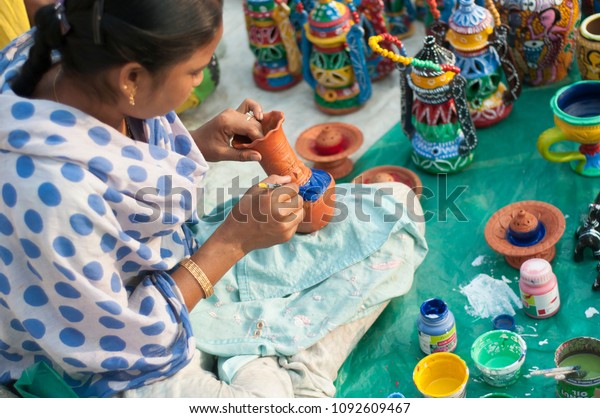 KOLKATA- NOVEMBER 26 :An Indian artisan painting on a flower pot  during the Handicraft Fair on 26th November, 2014 in Kolkata, India