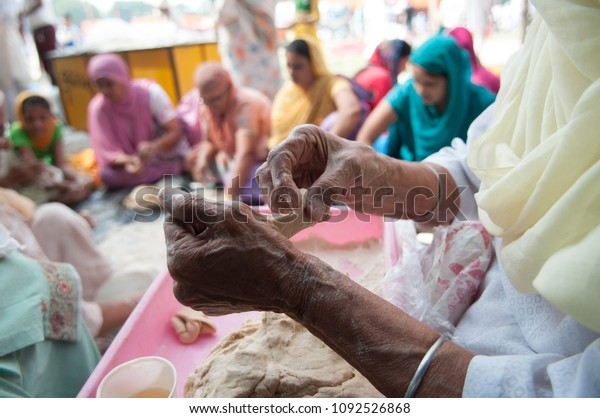 """KOLKATA- NOVEMBER 6:Old volunteers making """"roti"""" during a Langar or community kitchen service which in Sikhism refers to free meal for all  on 6th November, 2014 in Kolkata, India."""
