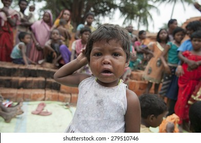 KOLKATA - OCTOBER 26 :  A small girl child crying while her family members and other residents is present in the background inside a brick factory on October 26, 2014 in Kolkata , India.