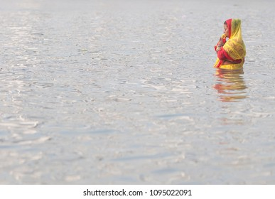 KOLKATA- OCTOBER 29:An woman half submerged in water offering prayers  during the Chhath Puja festival- A Hindu festival dedicated to the Sun God  29th October, 2014 in Kolkata, India.