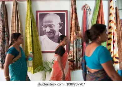 "KOLKATA -SEPTEMBER 26:Women walking past an image of Mahatma Gandhi during  the ""Tant"" saree Fair-A traditional Bengali saree  made in West Bengal and Bangladesh on September 26 2014 in Kolkata,India."
