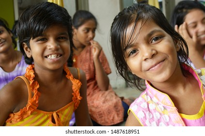 Kolkata, West Bengal - Aug 25 2019: Two pretty little girl children of india having a gala time enjoying themselves having fun and smiling facing the camera.