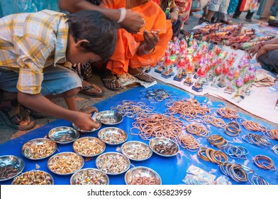 KOLKATA, WEST BENGAL , INDIA - 12TH AUGUST 2012 : Indian girl child choosing ornament products from out door local market place. India is booming with middle class consumers in society.