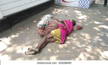 KOLKATA, WEST BENGAL, INDIA - 15 APRIL, 2017: An unidentified poor homeless Indian women sleeping at street.