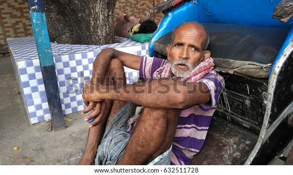 KOLKATA, WEST BENGAL, INDIA - 15 APRIL, 2017: An unidentified Indian poor old rickshaw puller sitting at his rickshaw at street.