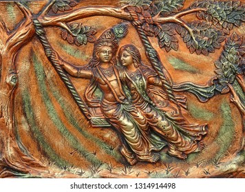 Kolkata, West Bengal / India - 22nd November 2018 : Decorative beautiful wall art of hindu god couple sri krishna and radha playful in vrindavan garden using a rocking cradle swing from a tree