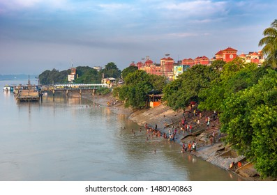 Kolkata, West Bengal/ India - August 11,2019.  A landscape view from Howrah Bridge of people taking holy bath in the River Ganges overlooking the  Howrah Railway Station.