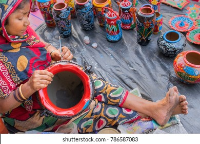 KOLKATA, WEST BENGAL , INDIA - DECEMBER 10 TH 2016 : Unidentified aged artist woman preparing colorful terracotta pots, works of handicraft, for sale during Handicraft Fair in Kolkata.