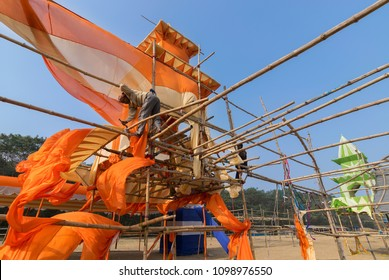 KOLKATA, WEST BENGAL, INDIA - JANUARY 18TH 2015 : Unknown labour dismantling a pandal (a temporary structure made of bamboo and safron clothes), at the end of Gangasagar Mela, Kolkata.