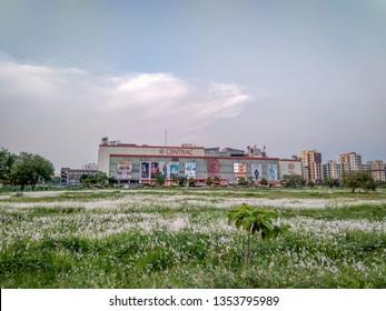 Kolkata, West Bengal / India - March 29, 2019: White wild flowers covering the field in front of the Central shopping mall ( in background ) at Newtown, Kolkata, West Bengal, India.