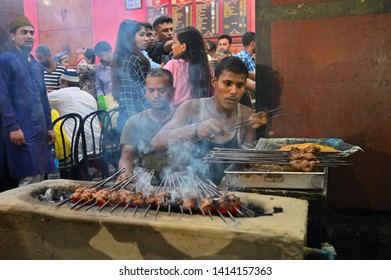 KOLKATA, WEST BENGAL, INDIA - MAY 27 2019 : Chicken seekh kababs are being grilled with heat in barbeque with metal skewers,at evening for sale as street food in Kolkata, India.