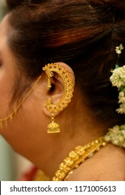 Kolkata, West Bengal, India - September 02 2018: A woman in her gold jwelley and ear shaped jwellery during Lord Krishna worshipping.
