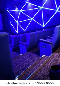 Kolkata, West Bengal/India - January 1, 2019: Blue seats or chairs and hall wall's and screen display under dim light inside INOX movie hall at Madhyamgram, Star Mall.
