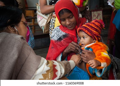Kolkata, West Bengal/India - January 13, 2013: An under five child and his mother came to see a doctor in a health clinic of a charity for check up.