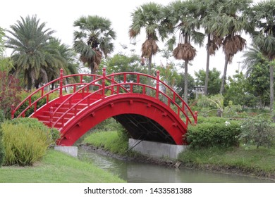 Kolkata, West Bengal/India - June 20, 2019: Beautiful large landscape with distance Red arc shaped Bridge, water lake and green nature  at 'Japanese Garden' inside 'Eco Park', Newtown.