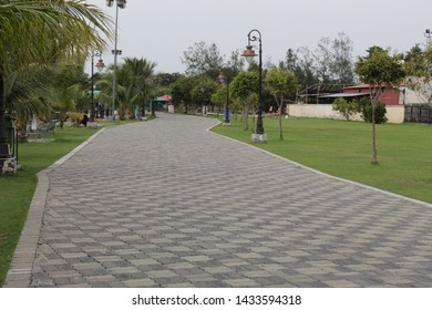 Kolkata, West Bengal/India - June 20, 2019: Empty large stone made pathway and nature field for public recreation at 'Eco Park', Newtown.