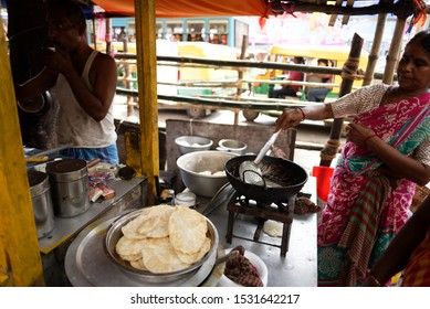 Kolkata, West Bengal,India-03.10.2019: Indian local lady street seller making snacks and selling to the customers in local shop in the street of Bengal. Indian lifestyle and culture.