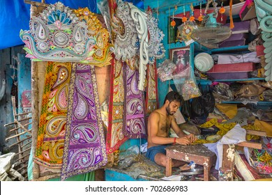 KOLKATA,INDIA, AUGUST 24,2017: An artisan works on decorative items used on Indian idols and deities in his workshop at Kumartuli area of Kolkata, India.