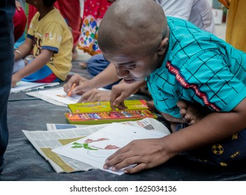 KOLKATA,INDIA,12/11/2019 Developmentally Disabled child is seeing and drawing on his paper at treatment center