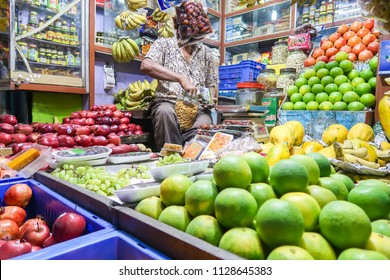 Kolkata,West Bengal/India - April 8,2018 : Variety colorful fresh fruit and man seller at local grocery shop , Lifestyle Indian people shopping food at night market