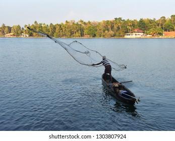 KOLLAM, KERALA, INDIA, JANUARY 29, 2019: A lone fisherman in a small canoe casting his fishing net in the backwaters of Ashtamudi lake in the morning.