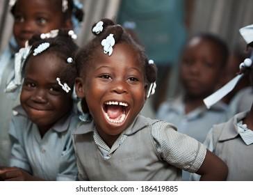 KOLMINY, HAITI - FEBRUARY 12, 2014 - Adorable Haitian school girl in her classroom laughing.