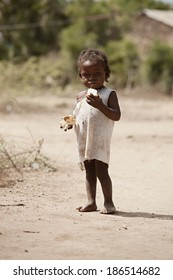 KOLMINY, HAITI - FEBRUARY 12, 2014. Undernourished Haitian child eating some peanut butter bread given to her by missionaries.