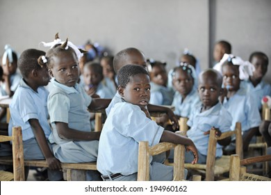 KOLMINY, HAITI:  FEBRUARY 12, 2014.  A classroom of unidentified elementary students.  Shallow depth of field with focus on front boy.