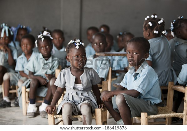 KOLMINY, HAITI - FEBRUARY 12, 2014 - Haitian classroom.  Shallow depth of field with focus on the young boy in the front.