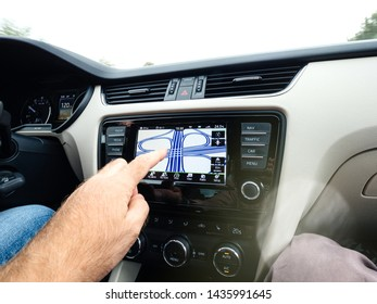 Koln, Germany - Aug 15, 2018: Man hand pointing at the multiple roundabout pattern on the car integrated GPS in the dashboard of German autobahn