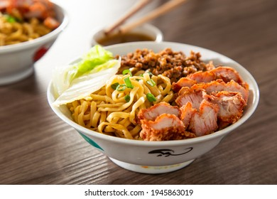 A Kolo Mee is a Sarawak Malaysian dish of dry noodles tossed in a savoury pork and shallot mixture, topped off with fragrant fried onions. - Shutterstock ID 1945863019