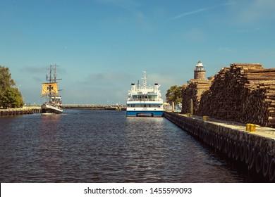 Kolobrzeg, Poland - 07.26.2018:MS Jantar awaits passengers at the Kolobrzeg harbor, next to the cargo terminal with lumber. MS Jantar sails between Kolobrzeg and the Danish island of Bornholm.