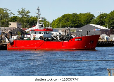 Kolobrzeg, Poland - June 06, 2018: One Fishing vessel whose hull is coloured red is moored by the quayside. It is marked with side number DZI-102