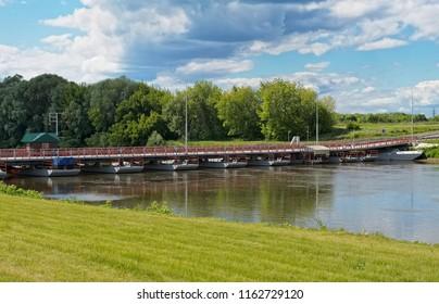 Kolomna, Russia - June 09, 2018: View of the Mityayevsky pontoon swing bridge across the Moskva River leading to Bobrenev the Theotokos-Nativity Monastery