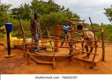 KOLONYI, UGANDA – OCTOBER 02, 2016: Children pumping water from a water well, is an excavation or structure created in the ground by digging or drilling to access groundwater in underground aquifers.