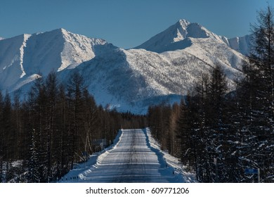 Kolyma track in winter against the background of snow-capped mountains