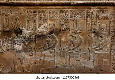 KOM OMBO, EGYPT - MARCH 18, 2010 : A wall at the Temple of Kom Ombo showing detailed relief engravings and hieroglyphs. On the left a pharaoh makes an offering to the gods Horus, Sobek and Isis.