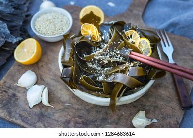Kombu kelp soaked seaweed salad with sesame seeds, lemon, garlic in bowl on wooden board. Japanese, Chinese, Korean traditional Asian food with chopsticks. Vegan vegetarian healthy food.