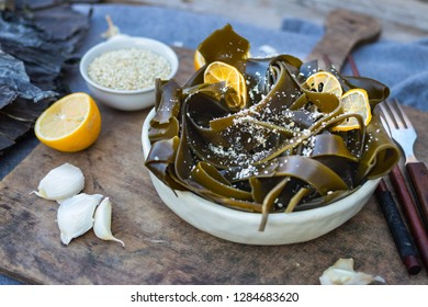 Kombu kelp soaked seaweed salad with sesame seeds, lemon, garlic in bowl on wooden board. Japanese, Chinese, Korean traditional Asian food with chopsticks. Vegan vegetarian healthy food.