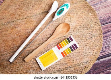 Kombucha brewing items, ph test strips, wooden spoon and thermometer