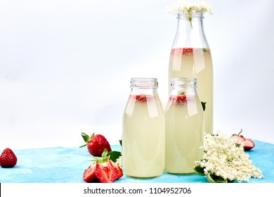 Kombucha tea with elderflower and strawberry on blue background. . Homemade fermented infused drink. Summer Healthy natural probiotic flavored drink. Copy space