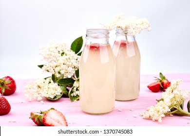 Kombucha tea with elderflower and strawberry on pink background. Homemade fermented infused drink. Summer Healthy natural probiotic flavored drink. Copy space