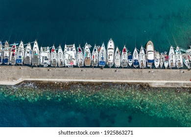 Komiza, Croatia - Aug 19 2020: Aerial overhead drone shot of boats in Adriatic sea dock on Vis Island in Croatia sunrise