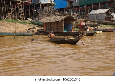 KOMPONG KLEANG, CAMBODIA - FEB 12, 2015 - Children in a small boat on the shore of Kompong Kleang floating fishing village,  Cambodia