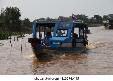 KOMPONG KLEANG, CAMBODIA - FEB 12, 2015 - Tourist boat travels along the waterway of Kompong Kleang floating fishing village,  Cambodia
