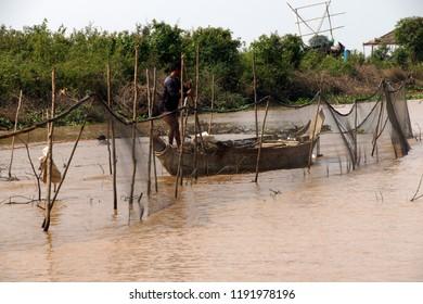 KOMPONG KLEANG, CAMBODIA - FEB 12, 2015 - Young man with fishing net, Kompong Kleang floating fishing village,  Cambodia