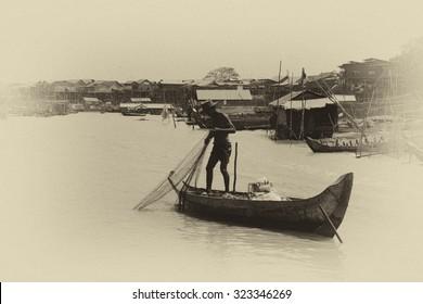 KOMPONG KLEANG, CAMBODIA - FEB 12, 2015 - Fisherman casting his net from a small boat, Kompong Kleang floating fishing village,  Cambodia