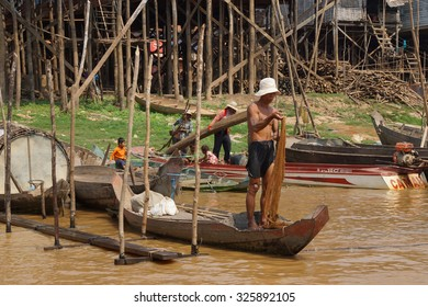 KOMPONG KLEANG, CAMBODIA - FEB 12, 2015 - Fisherman with fishing net, Kompong Kleang floating fishing village,  Cambodia