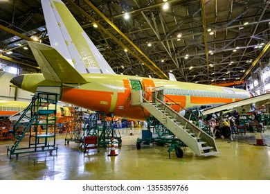 KOMSOMOLSK-ON-AMUR, RUSSIA — 1 March 2018, SСАC, Sukhoi Civil Aircraft Company, workshop where the fuselage of the regional jet Superjet 100 is assembled. view of the plane from the side with a ladder